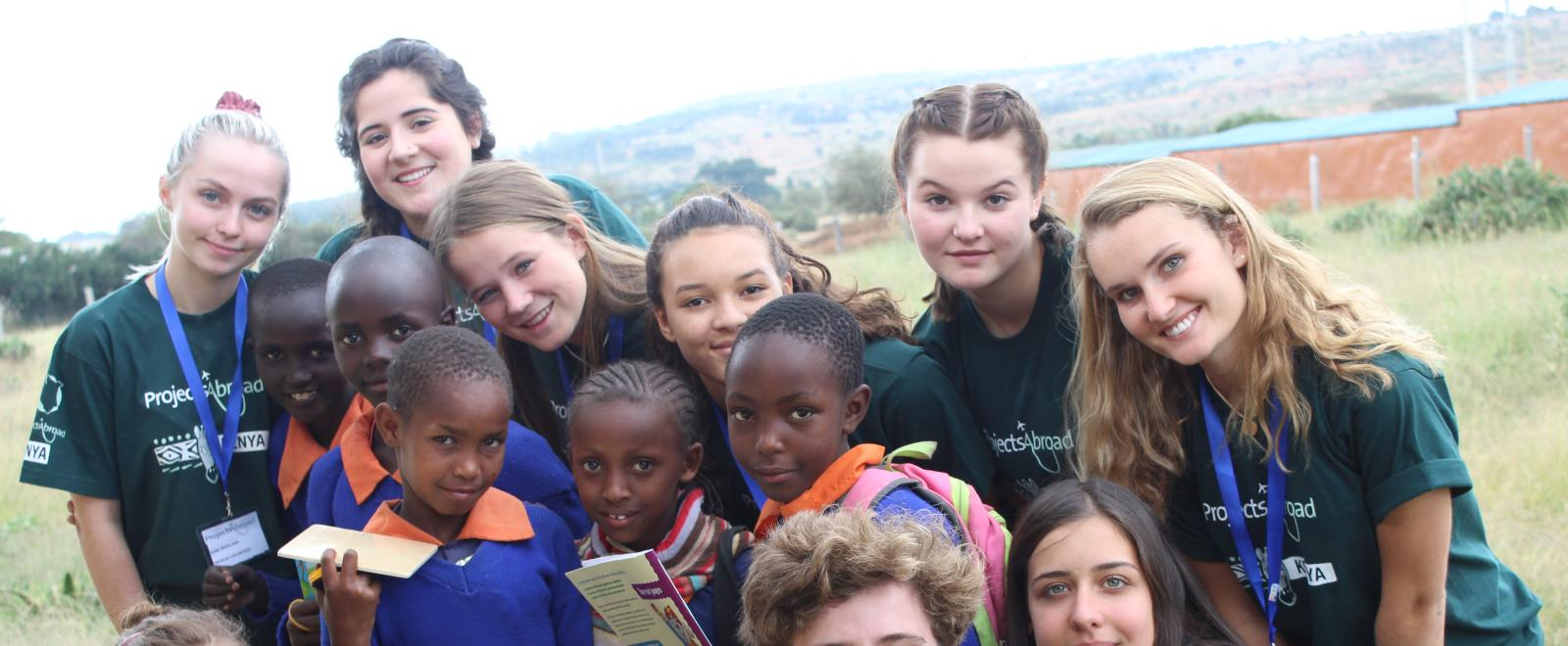 Healthcare volunteers take a group photo with students during a medical outreach in Kenya